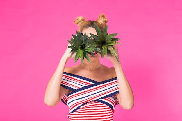 Portret kobiety śmieszne i ananas na różowym tle. lato, dieta i koncepcja zdrowego stylu życia.