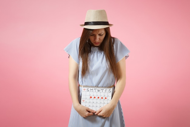 Portret kobiety smutne choroby w niebieskiej sukience gospodarstwa okresy kalendarza do sprawdzania dni miesiączki położyć rękę na brzuchu na białym tle na różowym tle. medycyna, opieka zdrowotna, koncepcja ginekologiczna. skopiuj miejsce.