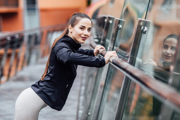 Portret kobiety, sportive sportowiec rozciągający się na schodach w centrum miasta panoramę miasta.