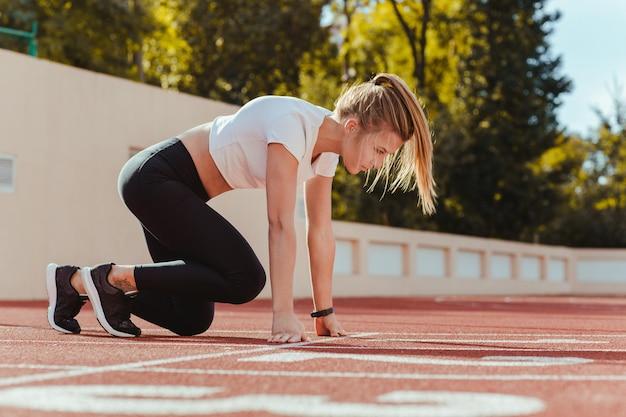 Portret kobiety sportowe w pozycji startowej do biegania