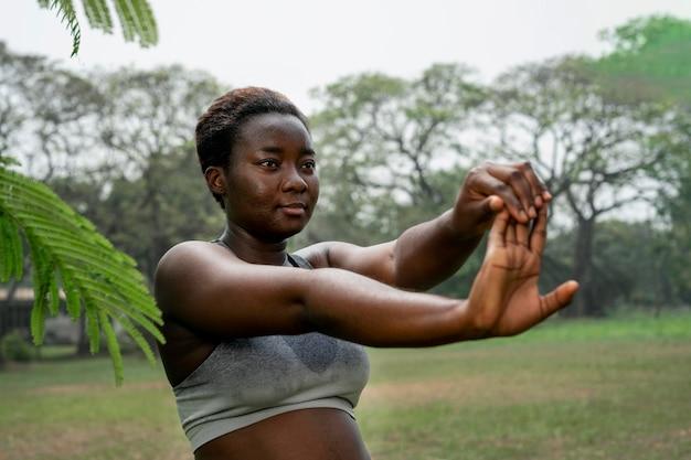 Portret kobiety sportowy w przyrodzie, rozciąganie