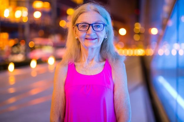 Portret kobiety starszy uśmiecha się na zewnątrz w nocy