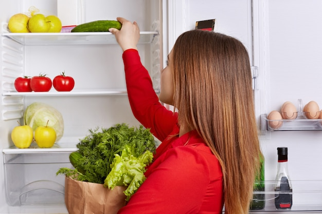 Portret kobiety stawia warzywa na półkach lodówki