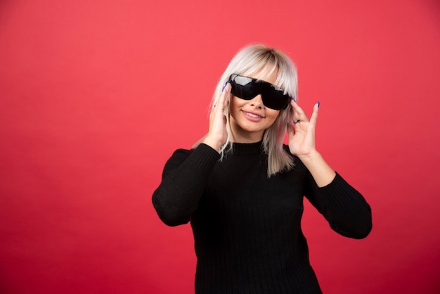 Portret kobiety stojącej i pozowanie w czarnych okularach na czerwonej ścianie.