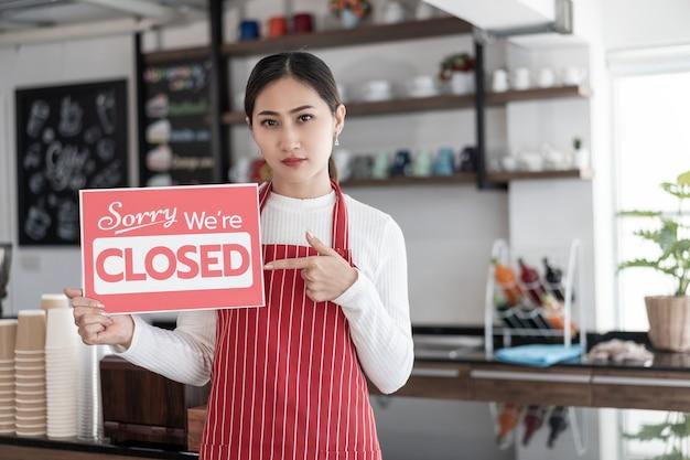 Portret kobiety stojącej kelnerka przy bramie jej kawiarni z pokazując zamknięty szyld