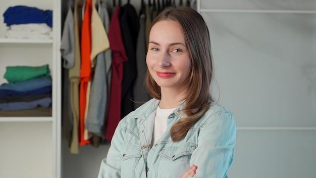 Portret kobiety stojącej na tle dużej garderoby szafa ze stylowymi ubraniami i artykułami gospodarstwa domowego.