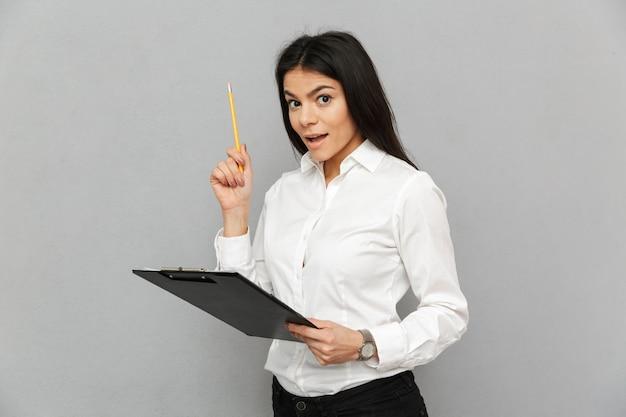 Portret kobiety sukcesu o długich ciemnych włosach na sobie strój biznesowy trzymając schowek z papierami i badanie dokumentów, na białym tle nad szarym tłem
