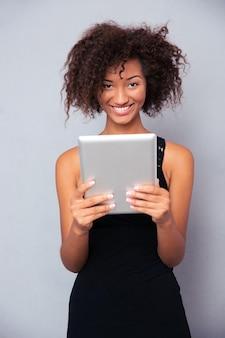 Portret kobiety szczęśliwy afro american przy użyciu komputera typu tablet na szarej ścianie