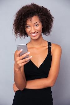 Portret kobiety szczęśliwy afro american za pomocą smartfona na szarej ścianie