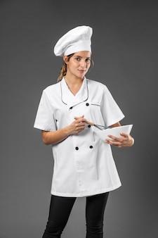 Portret kobiety szefa kuchni z mieszaniem miski