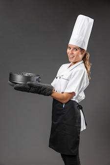 Portret kobiety szefa kuchni z patelni