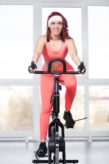 Portret kobiety szkolenia na rowerze w siłowni
