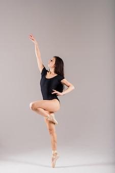 Portret kobiety tańczącej baletnicy w czarnym body w studio na szarym tle