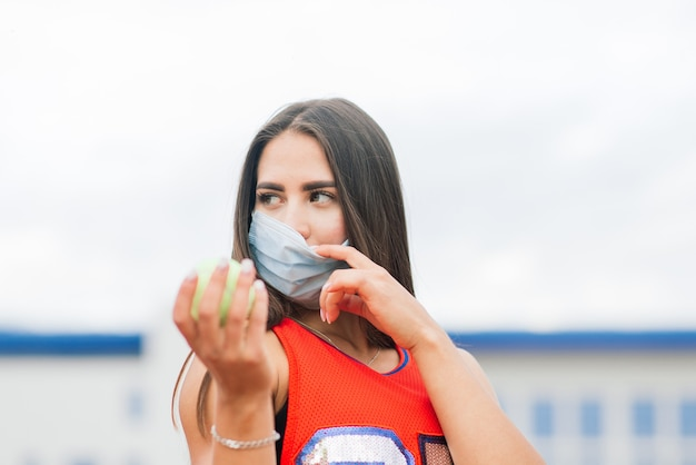 Portret kobiety tenisista trzyma piłkę na zewnątrz z maskami ochronnymi