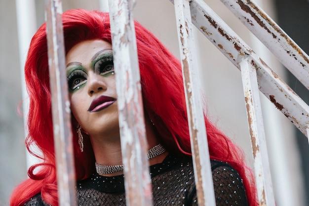 Portret kobiety transpłciowej, w czerwonej peruce, patrząc w górę, na balkonie.