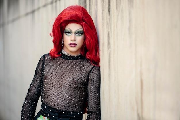 Portret kobiety transpłciowej, w czerwonej peruce, patrząc w kamerę, w tle ściany na ulicy.