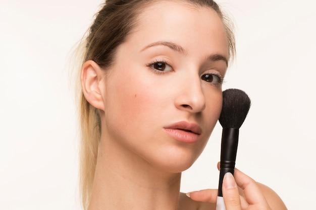 Portret kobiety trzyma pędzel do makijażu