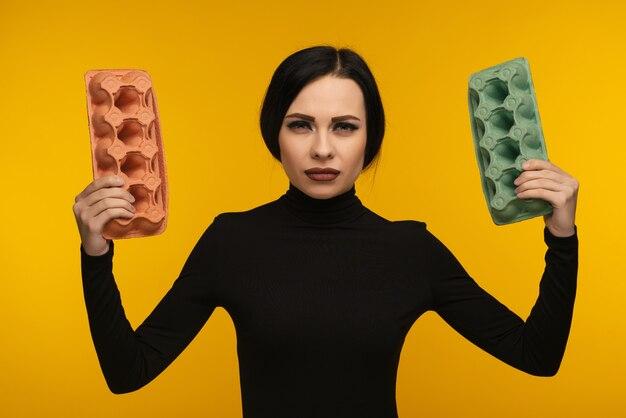 Portret kobiety trzymać karton na żółtym tle. pojęcie zanieczyszczenia środowiska przez ludzkie produkty odpadowe.