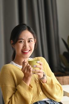 Portret kobiety trzymając się za ręce kubek gorącego napoju i uśmiecha się do kamery w biurze