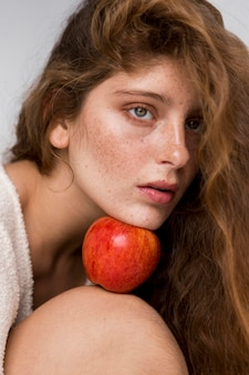 Portret kobiety trzymającej czerwone jabłko między jej twarzą a kolanem