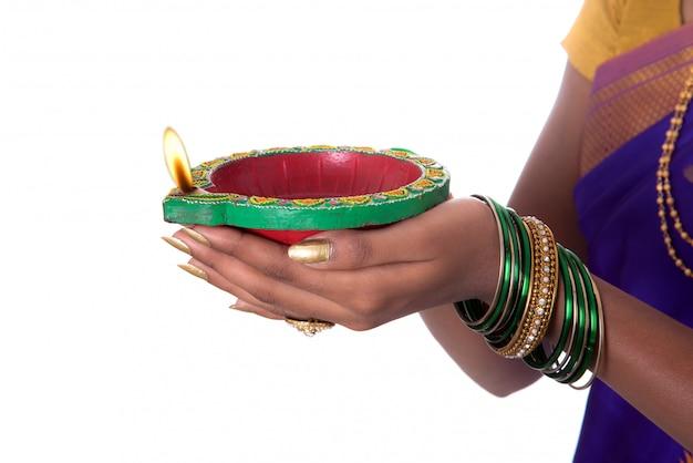 Portret kobiety trzymającej diya, diwali lub deepavali zdjęcie z żeńskimi rękami trzymającymi lampę naftową podczas festiwalu światła na białej ścianie