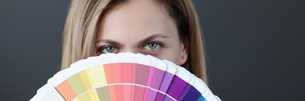 Portret kobiety trzymającej fana wyboru palety kolorów przez stylistę koncepcji schematu kolorów