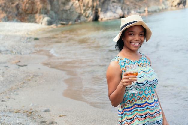 Portret kobiety trzymającej kieliszek wina. kobieta w sukni i kapeluszu. patrząc w kamerę.