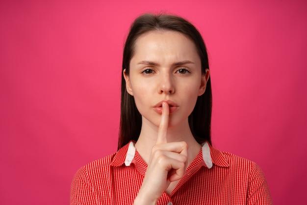 Portret kobiety trzymającej palec na ustach, aby milczeć na różowym tle