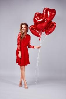 Portret kobiety trzymającej pęk balonów w kształcie serca