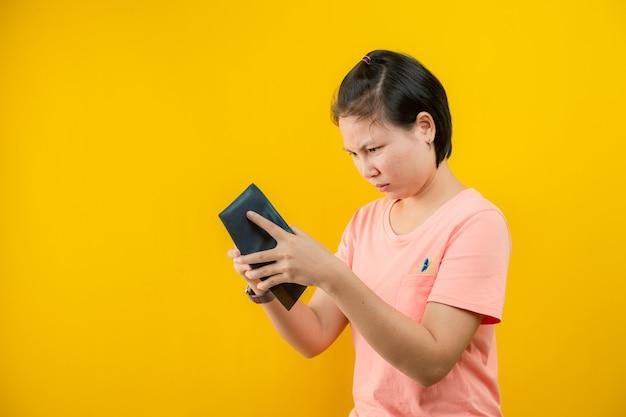 Portret kobiety trzymającej portfel, żałując, że nie ma pieniędzy w jej torebce przed żółtym oszczędzaniem background.concept.