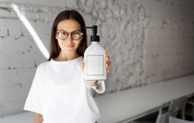 Portret kobiety trzymającej środek dezynfekujący
