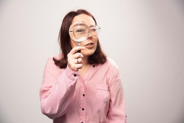 Portret kobiety trzymającej szkło powiększające na białym. zdjęcie wysokiej jakości