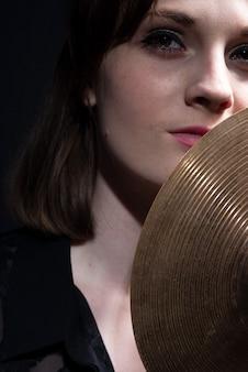 Portret kobiety trzymającej w dłoniach talerz bębna