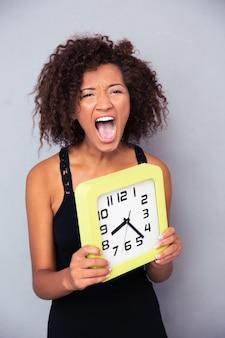 Portret kobiety trzymającej zegar i krzycząc na szarej ścianie