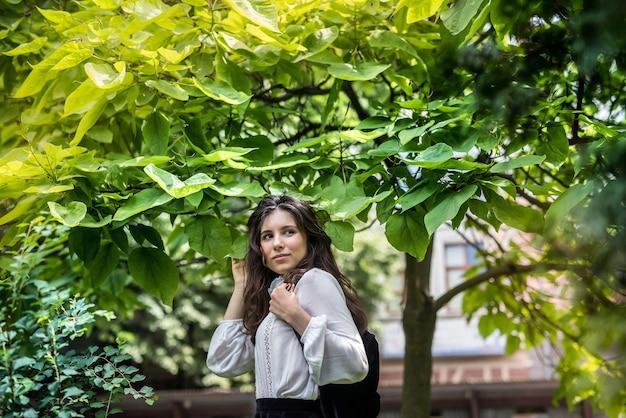 Portret kobiety ubranej w białą bluzkę i stylową czarną spódnicę w pobliżu zielonego drzewa, park miejski