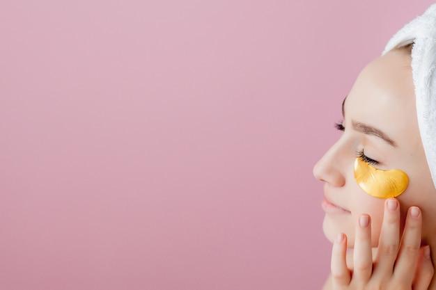 Portret kobiety uroda z plastry oczu. kobieta uroda twarz z maską pod oczami. piękna kobieta z naturalnym makijażem i złotymi płatkami kolagenu kosmetyków na świeżej skórze twarzy.