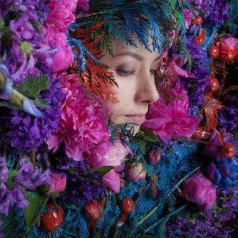 Portret kobiety w bajkowej stylizacji otoczony naturalnymi roślinami i kwiatami.