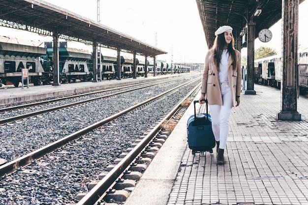 Portret kobiety w berecie i beżowej kurtce spacerującej z walizką przez stację kolejową.