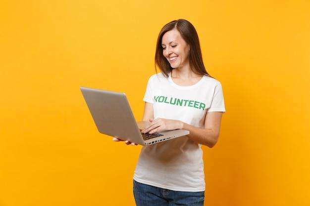 Portret kobiety w białej koszulce z napisem zielony tytuł wolontariusza przy użyciu komputera typu laptop pc na białym tle na żółtym tle. dobrowolna bezpłatna pomoc pomoc, koncepcja pracy łaski charytatywnej.