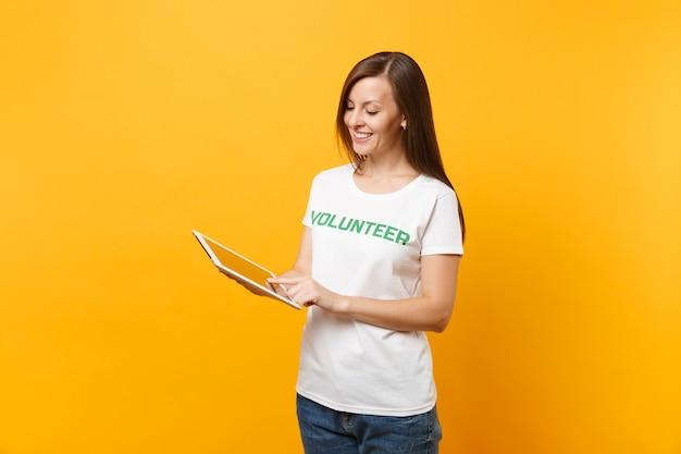 Portret kobiety w białej koszulce z napisem zielony tytuł wolontariusza przy użyciu komputera typu tablet pc na białym tle na żółtym tle. dobrowolna bezpłatna pomoc pomoc, koncepcja pracy łaski charytatywnej.