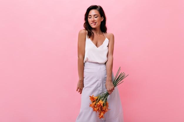 Portret kobiety w białej spódnicy i bluzce, trzymając kwiaty na na białym tle. ładna kobieta z bukietem w dłoniach zalotnie przygryza wargę.