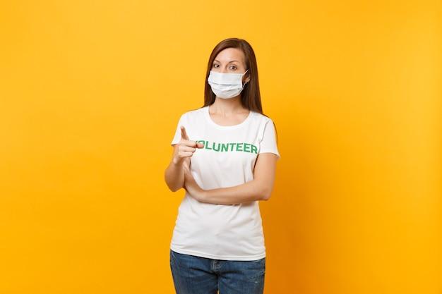 Portret kobiety w białej sterylnej masce do twarzy, t-shirt z napisem zielony tytuł wolontariusz na białym tle na żółtym tle. dobrowolna bezpłatna pomoc pomoc, koncepcja zdrowia łaski pracy charytatywnej.