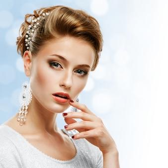 Portret kobiety w białej sukni i biżuterii.