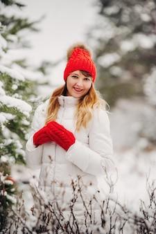 Portret kobiety w białych ubraniach i czerwonym kapeluszu w lesie mroźnej zimy. dziewczyna w zaśnieżonym lesie zimą