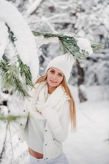Portret kobiety w białych ubraniach w lesie mroźnej zimy. dziewczyna w białym kapeluszu na głowie w zaśnieżonym lesie zimą.