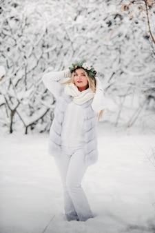 Portret kobiety w białych ubraniach w zimnym lesie. dziewczyna z wieńcem na głowie w zaśnieżonym lesie zimą.
