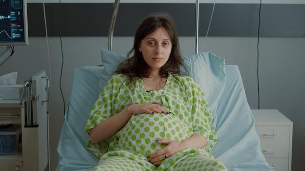 Portret kobiety w ciąży r. w łóżku na oddziale szpitalnym ze sprzętem medycznym przygotowującym do porodu na macierzyństwo. kaukaski pacjent trzymający rękę na brzuchu podczas siedzenia w oczekiwaniu na dziecko