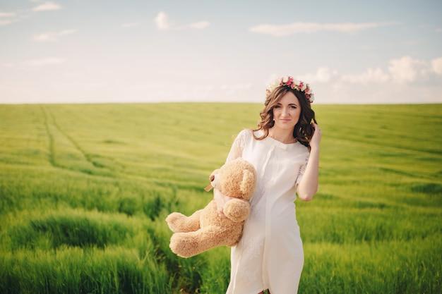 Portret kobiety w ciąży z misiem w ręku w polu trawy. młoda piękna ciężarna dziewczyna z wiankiem na głowie w słońcu. macierzyństwo. wiosna. kopia przestrzeń. selektywna ostrość