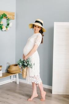 Portret kobiety w ciąży z wiklinowym koszem, kwiatami i słomkowym kapeluszem. portret zrelaksowanej, zadowolonej kobiety w ciąży.