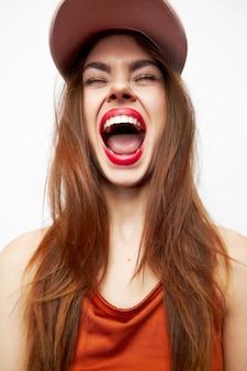 Portret kobiety w czapce zabawa usta szeroko otwarte zamknięte oczy czerwone usta